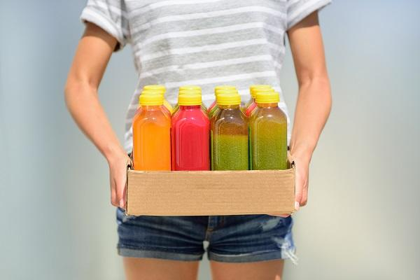 Woman holding delivery box of freshly cold pressed fruit and veg