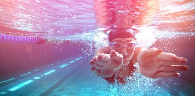 Athletic swimmer training on her own in the swimming pool at the
