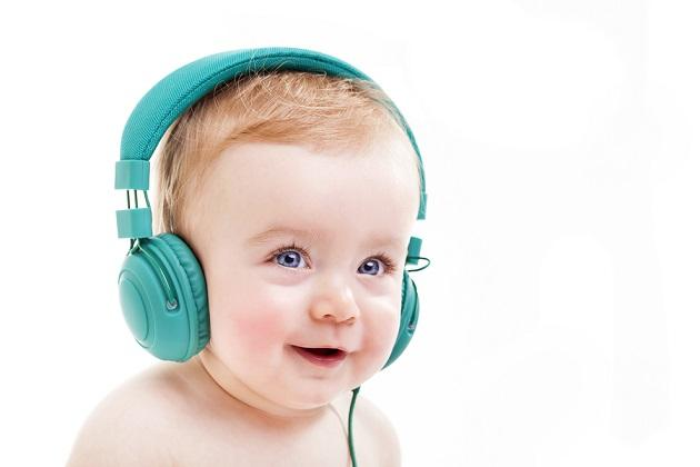 Smiling baby with headphones listening to music, isolated on whi